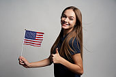 Happy female holding America flag and gesturing thumb up