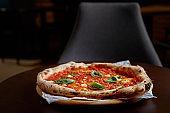 Food concept. Fresh original Italian pizza on a wooden board in Italian pizzeria or restaurant.