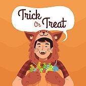 Boy in halloween costume holding pumpkin full of candies