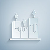 Paper cut Burning candles icon isolated on grey background. Cylindrical candle stick with burning flame. Paper art style. Vector Illustration