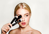 Portrait of beautiful blonde young woman face holding make up brushes. Spa model girl with clean skin isolated on a gray background