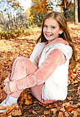 Autumn portrait of adorable smiling little girl child preteen in the park