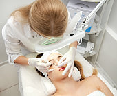 Woman getting facial beauty treatment in medical spa center