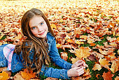 Autumn portrait of adorable smiling little girl child preteen lying in leaves