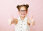 Portrait of funny little girl child wearing glasses isolated on a pink
