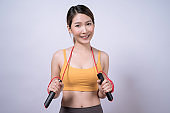 Asian woman holding rope skipping equipment isolated on white background, Healthy exercise ideas.