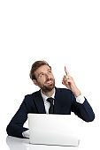 happy businessman in navy blue suit pointing finger above