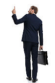 young businessman in navy blue suit pointing finger and holding suitcase