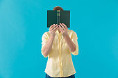 Young casual man hiding his face behind a book