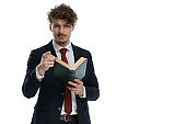 Charming businessman holding book and pointing