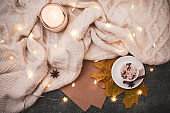 Top view, flat lay. Cozy knitted blanket, Christmas garland, small pumpkins, a cup of hot cappuccino with spices.