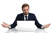 clueless young businessman in navy blue suit reading emails
