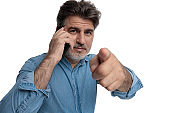 Confident casual man talking on his phone and pointing forward