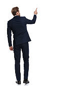 young businessman in navy blue suit pointing finger to side