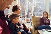 Portrait of small Caucasian boy three years old child sitting by his grandmother grandfather and mother family at home or restaurant in sunny day holding his shirt looking away side view