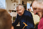 Portrait of senior man 80 years old pensioner sitting in chair with his family son and grandson at the restaurant or home retirement nursery grandfather caucasian
