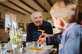 Portrait of old senior man pensioner grandfather sitting at the restaurant looking to his caucasian grandson son boy child taking food family nursery