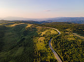Aerial view from above on the country road in mountain range in between green grass and trees around - nature travel concept drone photo on Tresibaba in Europe Serbia in sunny summer day