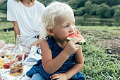 Close-up little girl eats watermelon outside.