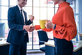 Business partners shaking hands with coffee cup.
