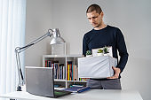 Front view of caucasian man holding box with his personal belongings at the office - Male adult being fired from work taking his stuff after losing job - recession economic financial crisis concept