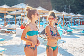 Two women female girls sisters or friends couple talking on the beach in the bikini swim suit in sunny summer day wearing sunglasses on the vacation
