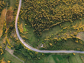 Aerial view top down from above on the country road in mountain range in between green grass and trees around - nature travel concept drone photo on Tresibaba in Europe Serbia in sunny summer day