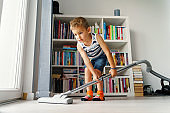 Little kid using vacuum cleaner at home - Small boy cleaning floor in apartment - Child doing housework having fun - side view full length in summer day - childhood development real people concept