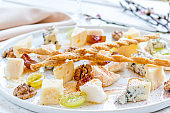 Cheese plate with nuts and honey italian food on white table