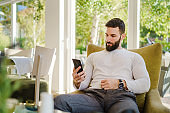 Portrait of adult good looking caucasian man sitting at cafe in day using mobile phone - Male with beard online date on internet while waiting sending love in video call - dating concept