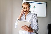 Portrait of young beautiful caucasian woman working at office. Blonde girl standing making a call. Front view of woman using phone at the office reading report. business and female empowerment concept