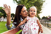 Young beautiful caucasian woman and baby daughter sitting on the bench in park in summer or autumn day waving to somebody - Single mother and child concept