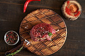 Fresh, juicy, aged fillet mignon steak tied with twine on a cutting board with spices - peas, dried tomatoes and paprika, red chili on a wooden surface. Top view, place for text