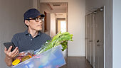 Chinese delivery man looking for customer's address via phone