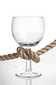 Wine glass tied with a rope. Concept of alcoholism and addiction