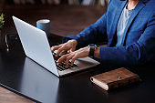 Businessman using laptop computer at home. Close up of male hands typing on laptop keyboard in office. Business, working from home, studying online concept. Blogger, journalist writing new article