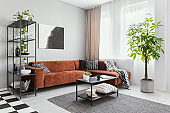 Trendy living room interior with brown corner sofa with black and white pillows and industrial coffee table