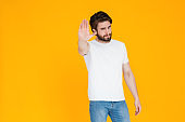 A disgruntled serious young bearded man in his 30s in a white t-shirt poses showing a stop gesture with the palm of his hand looking at the camera. isolated on a bright yellow wall background Studio portrait