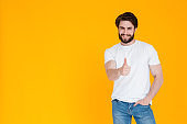 a happy bearded young man in a white t-shirt and blue denim trousers smiles at the camera and shows a like gesture. body language thumbs up on a yellow background