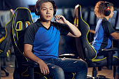 Failure. Portrait of asian guy, male cyber sport gamer wearing headphones looking at PC screen with confused face while playing online video games