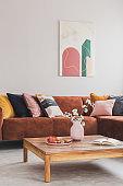 Comfortable brown velvet sofa with pillows in elegant living room interior