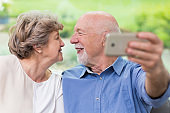 Modern grandpa and grandma looking for each other and taking selfie for social media account