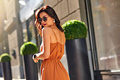 Fashion girl. Young beautiful and stylish caucasian woman wearing long romantic dress and eyeglasses looking at camera while standing on the city street
