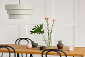 Flowers in glass vase,coffee cup on wooden dining table