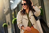 Enjoying warm day. Young stylish and happy woman wearing eyeglasses looking aside and smiling while walking city streets