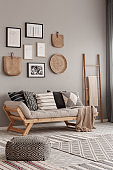 Beige scandinavian settee with patterned pillows in stylish living room interior