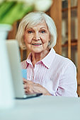 Positive gray haired lady working with computer in the room
