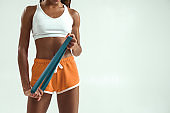 Fitness equipment. Cropped photo of slim african woman in sport clothes holding resistance band while standing in studio against grey background