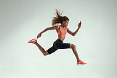 Never stop run. Full length of young african woman with perfect body in sports clothing jumping in studio against grey background