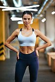 Portrait of a young beautiful fitness woman in sportswear looking at camera while standing at gym, vertical shot
